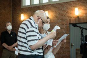 Ein Mann und eine Frau stehen an einem Mikrofon und verlesen einen Gebetstext bei der Einführung von Pastorin Anja Vollendorf
